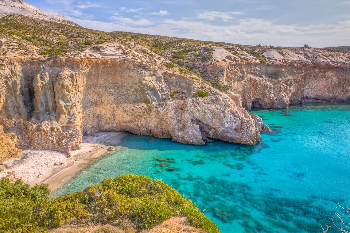 a secluded beach in Milos seen from the top of a cliff