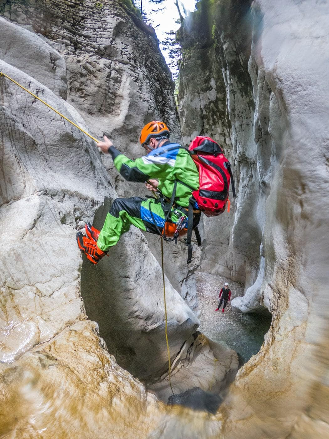 a guide hanging off a ledge while canyoning in val noana trentino